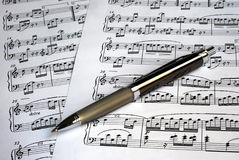 A pen on the top of music sheets Stock Photos