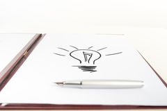 Pen on Top of Paper with Light Bulb Drawing Royalty Free Stock Photo