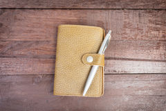 Pen on top of yellow organizer with leather cover on wooden background. Stock Photography