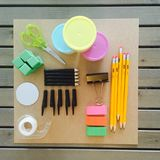 Organized tinker stem supplies on paper square and wood table. Pen tops, pencils, cubes, erasers, scissors, tape, and pencils ready to tinker Royalty Free Stock Image
