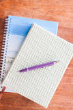 Pen and two of notebooks on wooden table Stock Images