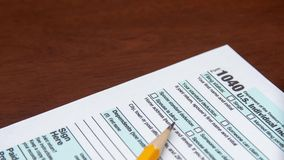 Pen on US TAX form Background. Tax Day concept. stock video footage