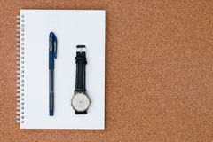 Pen and watch place on note book on a wooden background Stock Photo
