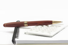 Pen and white calculator on the notepad. Pen and white calculator on the spiral notepad Royalty Free Stock Photo