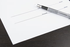 Pen and white sheet on a brown table Royalty Free Stock Photo