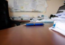 Pen on wood desk. Blue pen on wood desk in office Royalty Free Stock Images