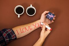 Pen write letter dear red i love you hand coffee cup gift box brown Valentine`s Day. Pen to write a letter dear. a female hand writes I love you on a man`s hand Stock Photos