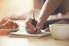 Pen writing on notebook with coffee Stock Photos
