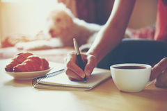 Pen writing on notebook with coffee Stock Photo
