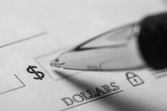 Pen Writing op een Blanco cheque - sluit omhoog stock afbeeldingen
