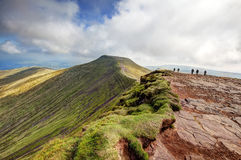 Pen y Fan from Corn Du. BRECON, WALES - SEPTEMBER 07, 2014 : People walking towards the peak of Pen y Fan from the top of Corn Du in the Brecon Beacons in Wales royalty free stock image