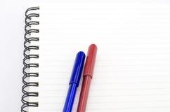 Pena azul e vermelha com o caderno isolado no branco Foto de Stock Royalty Free