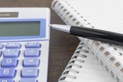 Pena, bloco de notas, e calculadora na tabela de madeira Imagem de Stock