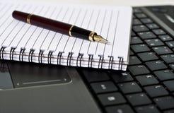 Pena, bloco de notas e portátil na mesa Fotos de Stock Royalty Free