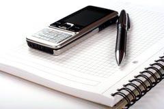 Pena, bloco de notas espiral e telefone móvel Imagem de Stock Royalty Free