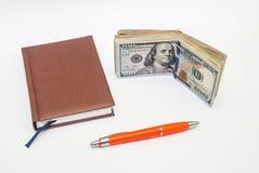 Pena, caderno, notas de dólar Fotos de Stock Royalty Free
