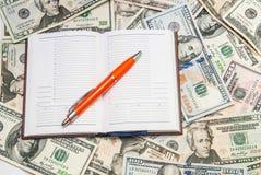 Pena, caderno, notas de dólar Fotografia de Stock Royalty Free