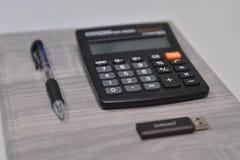 A pena, a calculadora e o usb colam no escritório Foto de Stock Royalty Free