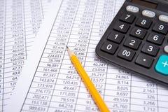 Pena, calculadora e vidros do negócio na carta financeira, conceito do negócio foto de stock