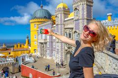 Pena Castle photography. Happy woman takes photo of Pena National Palace in Sintra, by mobile phone with Portugal flag cover. Tourism and travel in Portugal Stock Images