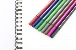 Pena colorida com o caderno isolado no branco Foto de Stock Royalty Free