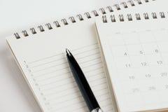 Pena com a almofada do calendário e de nota com lista de número para o conceito do lembrete, da tarefa e do planeamento do evento fotos de stock royalty free