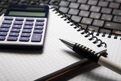 Pena com calculadora em um caderno e em um teclado fotografia de stock royalty free