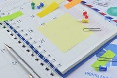 Pena com notas de post-it e pino na página do diário do negócio Imagens de Stock