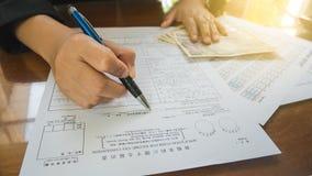 A pena da posse da mão da mulher de negócio preenche os detalhes no papel dos formulários de imposto no conceito do negócio com a Imagens de Stock Royalty Free