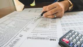 A pena da posse da mão da mulher de negócio preenche os detalhes no papel dos formulários de imposto no conceito do negócio Imagens de Stock