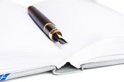 Pena da tinta e um caderno Foto de Stock Royalty Free