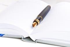 Pena da tinta e um caderno Fotografia de Stock