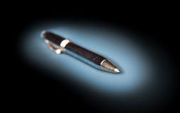 Pena de ballpoint do metal em um fundo escuro Fotografia de Stock Royalty Free