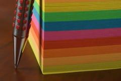 Pena de Ballpoint e notas coloridas Foto de Stock