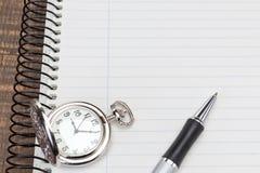 Pena de esferográfica do relógio de bolso no caderno para notas. Foto de Stock