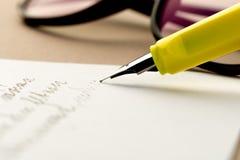 Pena de fonte amarela que escreve uma letra, vidros atrás fotografia de stock