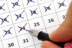 Pena de fonte em dias da marcação da mão da mulher no calendário Imagens de Stock
