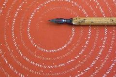 Pena de fonte no fundo de papel textured vermelho com teste padrão abstrato das letras Acessórios da escrita do projeto do vintag Imagens de Stock