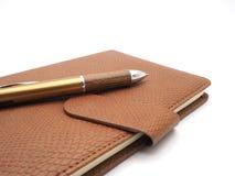 Pena de madeira com o livro do couro sintético no fundo branco Fotografia de Stock