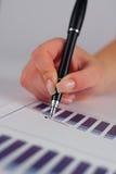 Pena de terra arrendada fêmea da mão sobre o gráfico de negócio Fotos de Stock Royalty Free