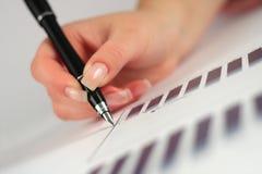 Pena de terra arrendada fêmea da mão sobre o gráfico de negócio Imagens de Stock Royalty Free