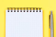Pena do caderno e de ballpoint no fundo amarelo. imagem de stock royalty free