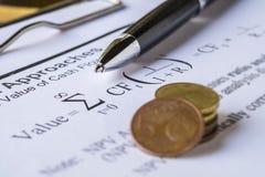 A pena e as moedas no fluxo de caixa do disconto modelam Fotografia de Stock Royalty Free