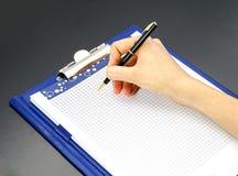 Pena e bloco de notas da mão da mulher foto de stock