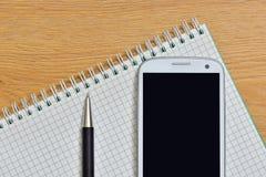 Pena e bloco de notas do telefone Fotografia de Stock
