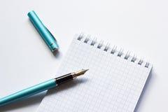 Pena e caderno de fonte no fundo branco, close-up imagens de stock royalty free