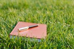 Pena e caderno na grama Imagens de Stock Royalty Free