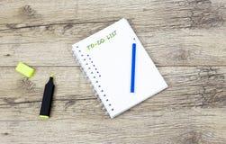 Pena e cadernos de marcador na placa de madeira escrita: Para fazer a lista imagem de stock