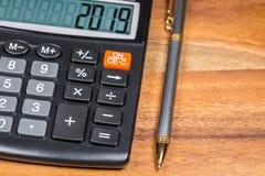 Pena e calculadora com número 2019 na exposição na tabela de madeira Fotos de Stock