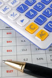 A pena e a calculadora de esfera põr sobre um formulário de dados Imagem de Stock